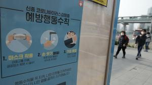 People wearing face masks walk near a banner showing precautions against the new coronavirus at a bus stop in Seoul, South Korea (Lee Jin-man/AP)