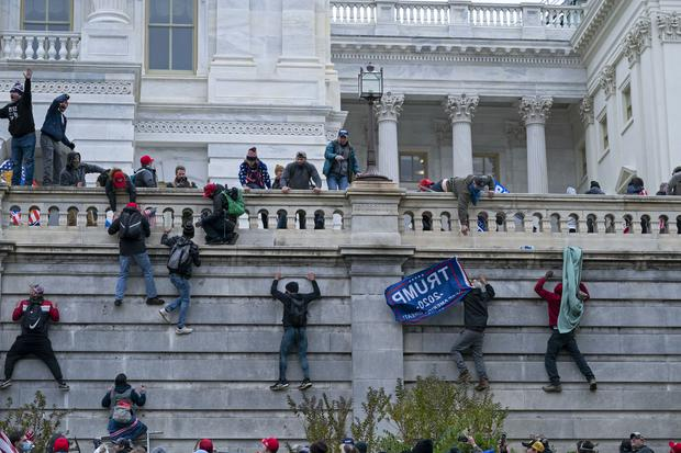Rioters climb the west wall of the the US Capitol in Washington in the January 6 insurrection (Jose Luis Magana/AP)