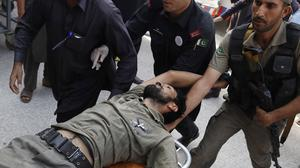 Pakistani security officials rush an injured colleague to hospital in Peshawar. (AP)