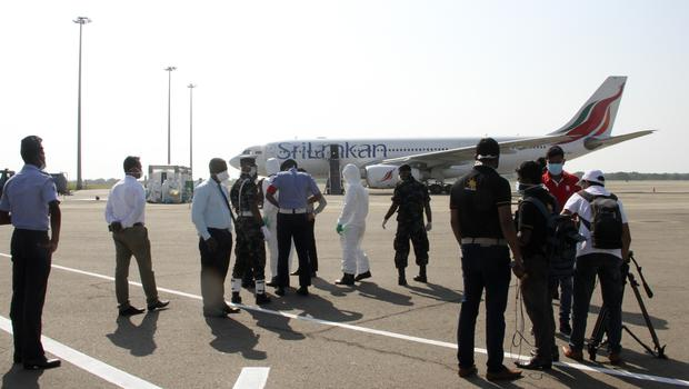 Sri Lankan air force officers, in protective gear, engage in disinfection procedures after a charted aircraft carrying Sri Lankan students evacuated from Wuhan province in China landed at the Mahinda Rajapaksa International Airport in Mattala (Dilip Nuwan Jayasekera/AP)