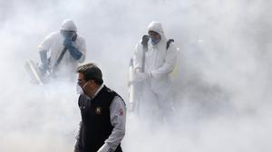 Firefighters disinfect a street against the new coronavirus in western Tehran (AP)