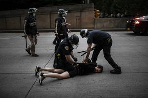Police deal with a protester who refused to observe New York's curfew on Tuesday (Wong Maye-E/AP)