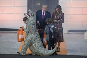 President Donald Trump and first lady Melania Trump give sweets to children (Alex Brandon/AP)