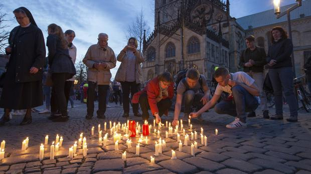 People light candles during a memorial service in front of Munster Cathedral (Friso Gentsch/dpa via AP)