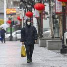 A man wearing a face mask walking in Wuhan (Chinatopix via AP)