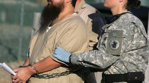 A prisoner is transported by a woman guard at Guantanamo (AP)