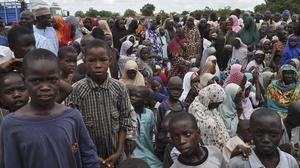 Civilians who fled their homes following an attack by Islamist militants in Bama take refuge at a school in Maiduguri, Nigeria (AP)