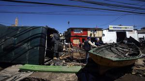 A boat and bus lay among the debris left behind by an earthquake-triggered tsunami in the coastal town of Coquimbo (AP)