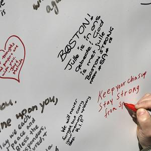 A woman writes on a message board at a makeshift memorial near the Boston Marathon finish line in Boston's Copley Square (AP Photo)