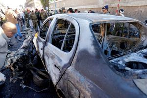 A police investigator looks at a damaged car at the scene of a car bomb outside the police college in Sanaa, Yemen