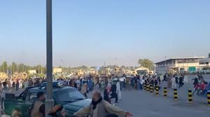 A horde of people run towards the Kabul Airport Terminal, after Taliban insurgents took control of the presidential palace in Kabul. Photo: Jawad Sukhanyar/via REUTERS