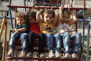 Children sit on a Ferris wheel during Eid celebrations in the Al-Fardous neighbourhood of Aleppo, which has been bombed repeatedly by Assad regime warplanes