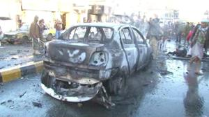 In this framegrabbed image from footage shot by AP Television News, a damaged car sits in the road after a suicide bomber driving a minibus full of explosives killed more than a dozen people Wednesday morning near a police academy in the heart of Yemen's capital, Sanaa, security officials said