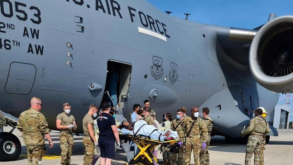 Medical support personnel help an Afghan mother, whose identity has been digitally obscured at source, with her family off a U.S. Air Force C-17 transport aircraft, call sign Reach 828, moments after she delivered a child aboard the aircraft upon landing at Ramstein Air Base, Germany, August 21, 2021. U.S. Air Force/Handout via REUTERS