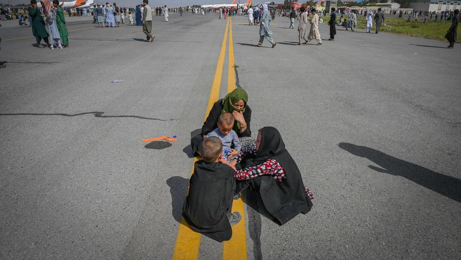 Afghan people sit along the tarmac as they wait to leave the Kabul airport in Kabul. Picture: Getty