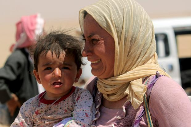 A displaced woman and child from the minority Yazidi sect, fleeing violence from forces loyal to the Islamic State in Sinjar town