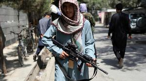 A Taliban fighter stands guard at a checkpoint in the Wazir Akbar Khan neighborhood in the city of Kabul, Afghanistan