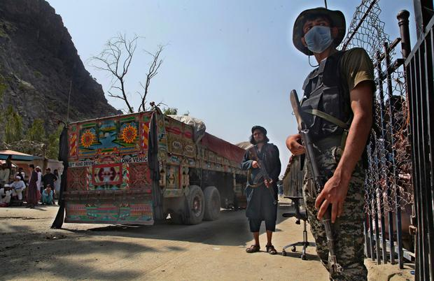 A Pakistani paramilitary soldier, right, and Taliban fighter, stand guard on their respective sides while a truck moves to cross at a border crossing point between Pakistan and Afghanistan AP Photo/Muhammad Sajjad)