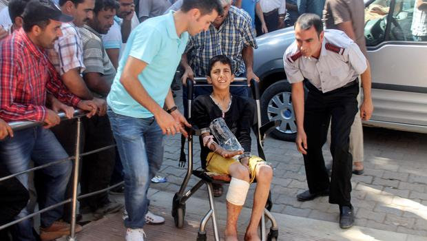 Wounded people are brought to the local hospital in Suruc in Turkey's Sanliurfa province, across the Syrian border town of Kobane yesterday.