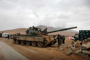 Syrian regime fighters take position as they advance on the ancient city of Palmyra yesterday