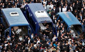 The bodies of Aryeh Kopinsky (C), Calman Levine (L) and Avraham Shmuel Goldberg lie in vehicles during their funeral near the scene of an attack at a Jerusalem synagogue (REUTERS/Baz Ratner)