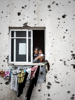 A mother and her child look out from her Gaza City apartment which has been badly damaged from artillery fire. Photo: Mark Condren