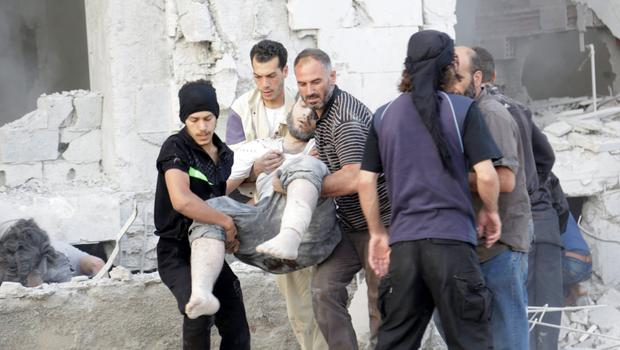 Residents carry an injured man at a site damaged by what activists said was a barrel bomb dropped by forces loyal to Syria's president Bashar Al-Assad in Maarat Al-Nouman, south of Idlib . . REUTERS