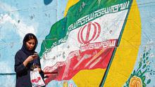 Banner: A woman walks past a mural of the Iranian national flag in a street in Tehran. Photo: Getty