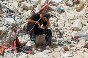 A man sits in the rubble after an attack in Aleppo, Syria.