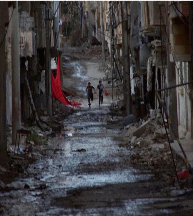 People run down a street in the war-torn city of Deir al-Zor, in eastern Syria