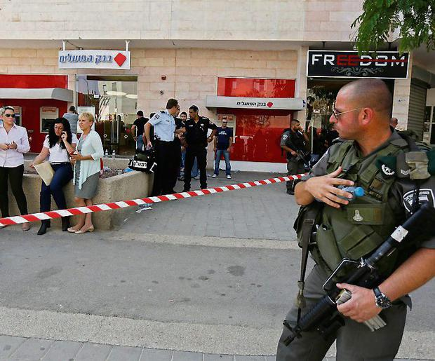 An Israeli policeman stands guard at the scene of a shooting at a Bank Hapoalim branch in the southern city of Beersheba May 20, 2013. A gunman shot dead four people execution-style in the bank in Israel on Monday after being refused an overdraft and cash from its automatic teller machine. The assailant, identified by media reports as a former paramilitary border policeman, killed himself after police raided the branch to free his hostages. REUTERS/Amir Cohen