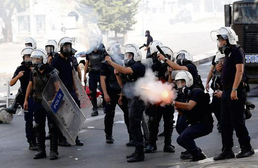 Riot police fire tear gas against protesters during a demonstration in Ankara