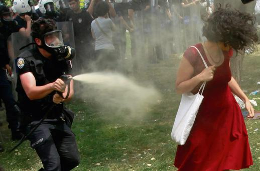 A Turkish riot policeman uses tear gas against a woman as people protest against the destruction of trees in a park brought about by a pedestrian project, in Taksim Square in central Istanbul