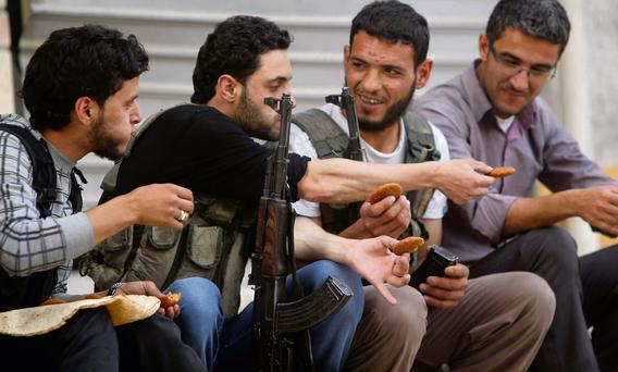 Free Syrian Army fighters eat Kibbeh, a traditional Allepian food, in Aleppo's Karm al-Jabal district