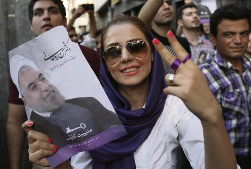 A supporter of Iranian president-elect Hassan Rowhani holds up his poster and flashes a victory sign during a celebration in Tehran