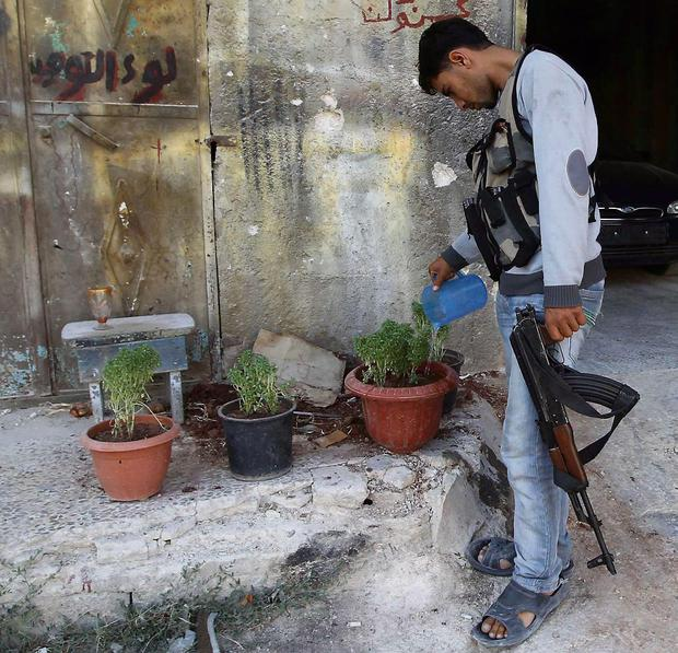 RESPITE: A rebel soldier waters plants on war-torn streets