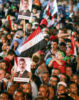 Supporters of deposed Egyptian president Mohammed Morsi attend a protest outside Rabaa Adawiya mosque in Cairo. The posters reads, 'no substitute for the legitimacy'