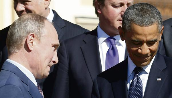 Russian President Vladimir Putin walks past US President Barack Obama during a group photo at the G20 Summit in St Petersburg.