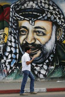 A young man walks past a mural of Yasser Arafat in Gaza city