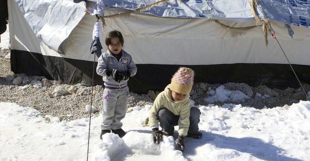 Syrian refugee children play with snow in a Syrian Refugee camp on the Lebanese border town of Arsal