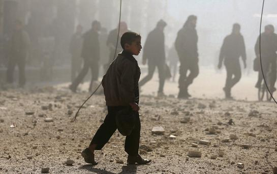 A young Syrian boy walks through the dust in Apello after an attack thought to be by forces loyal to the regime of Bashar al-Assad.