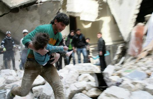 A man carries a child injured in a shelling attack in Aleppo, Syria, yesterday
