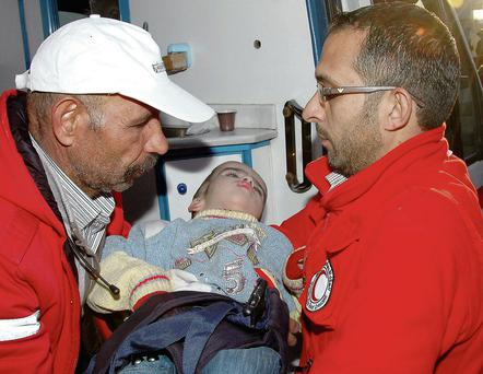 Red Crescent workers carry a child as they offer help at a shelter in the troubled city of Homs in Syria
