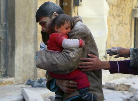 A boy holds his baby sister saved from under rubble, who survived what activists say was an airstrike by forces loyal to Syrian President Bashar al-Assad in Masaken Hanano in Aleppo yesterday. Photo: Reuters.