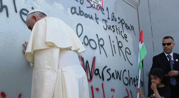 Pope Francis touches the wall that divides Israel from the West Bank