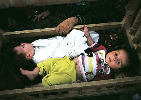 An Iraqi mother rocks her twin babies to sleep in the back of a truck after she was turned back from the border in Khazair, Iraq. Photo: Getty Images