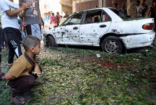 A Palestinian boy looks at a damaged car at the scene of an explosion at a public garden in Gaza City