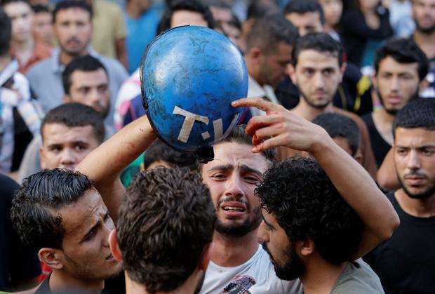 Palestinian freelance photographer Motaz Al Salhy cries as he holds the bloodied helmet of his friend Credit: Ted Botha