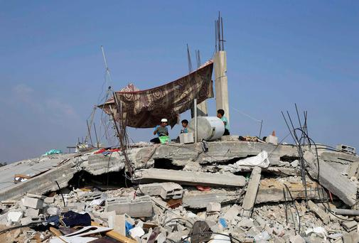 Palestinian children sit atop the remains of their house, which witnesses said was destroyed in the Israeli offensive, during a 72-hour truce in Khan Younis the southern Gaza Strip