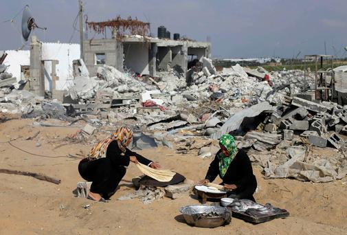 Palestinian women bake bread in front of the remains of their house, which witnesses said was destroyed in the Israeli offensive, during a 72-hour truce in Khan Younis the southern Gaza Strip